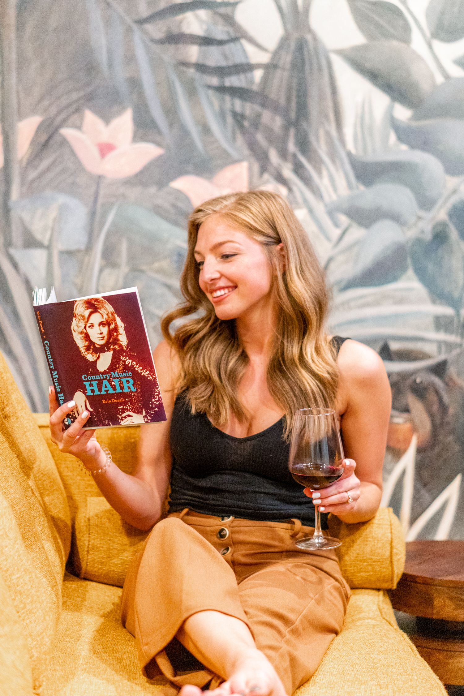 Girl sitting on yellow couch reading book and drinking wine