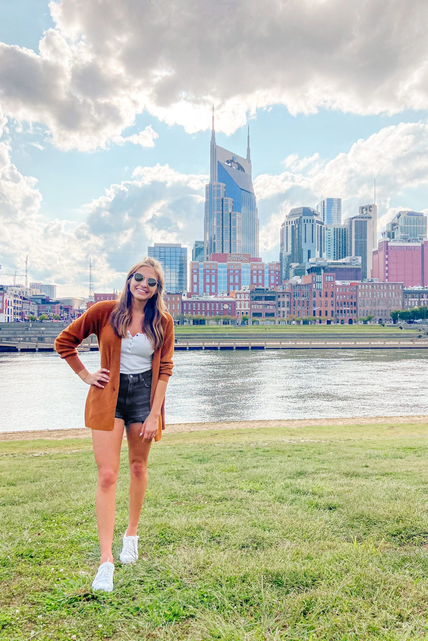 Girl standing on the grass with nashville cityscape in the background