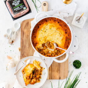 Vegan Shepherd's Pie on a cutting board with white napkins, beyond beef, and chives around it