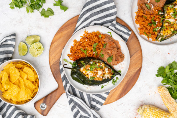 Elote Street Corn Stuffed Poblano Peppers plated with refried beans and spanish rice